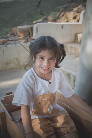 Portrait of a smiling girl sitting outdoors