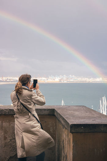 Rear view of woman photographing rainbow over sea against sky