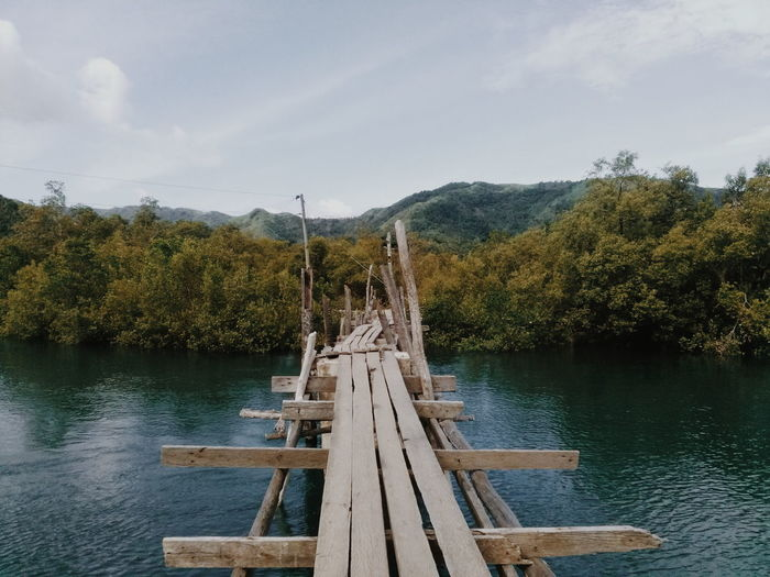 Old footbridge over river against mountains