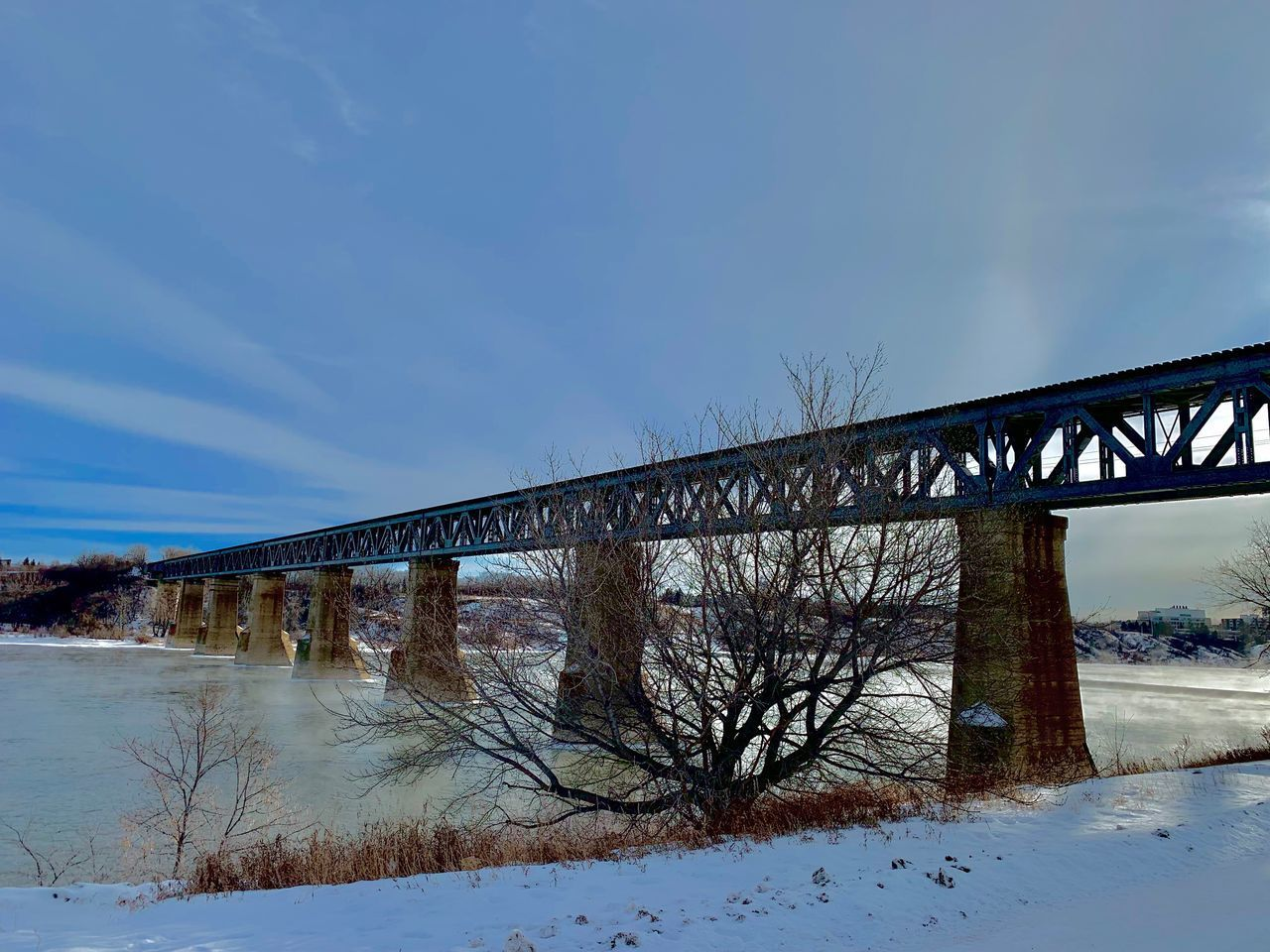 ARCH BRIDGE OVER RIVER AGAINST SKY DURING WINTER