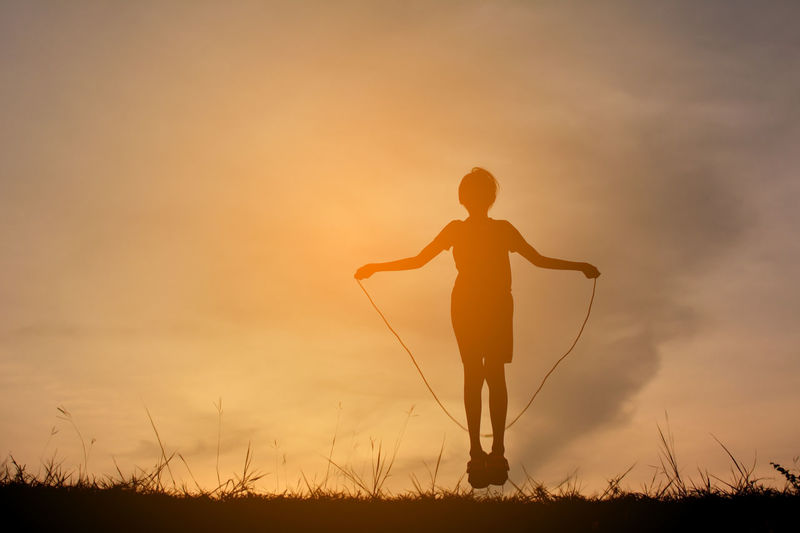 Silhouette Girl Playing Skipping On Field Against Sky During Sunset