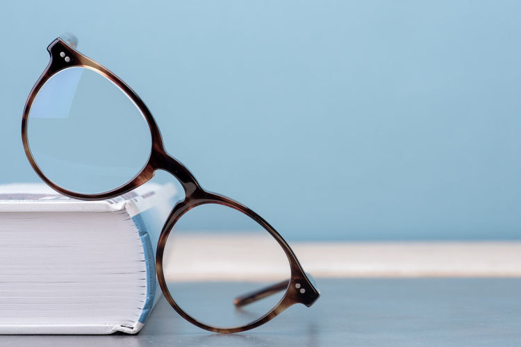 Glasses with book education and knowledge concept picture Glasses Eyeglasses  Still Life Personal Accessory Table Close-up Blue Book Education Wisdom Reading Literature Studying School Library Learning Knowledge Concept Collage Copy Space