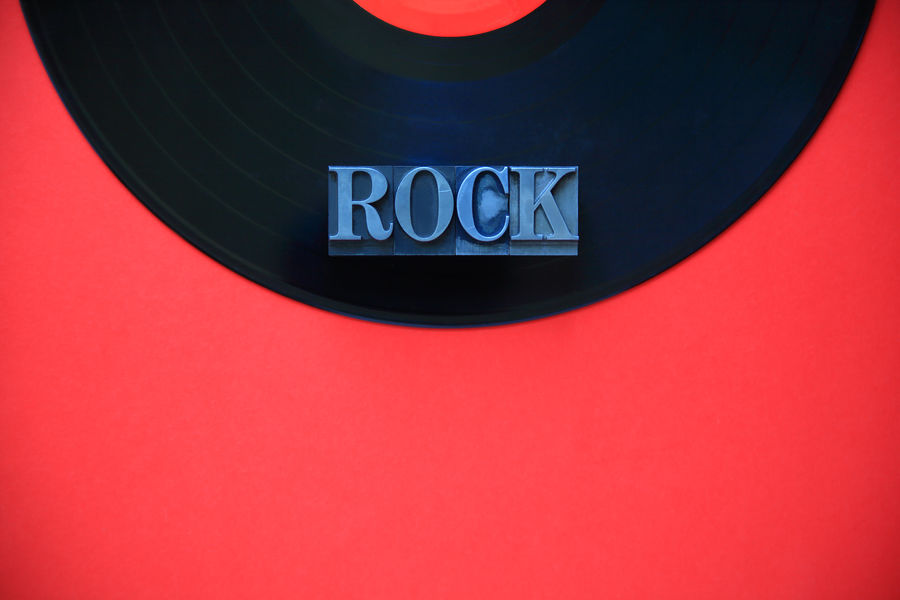 Vinyl record with rock word on red background Audio Black Close-up Communication Copy Space Day Gray Indoors  Letters Metal Type Music Music Category Natural Light No People Overhead Red Rock Round Semicircle Vintage Vinyl Record Word