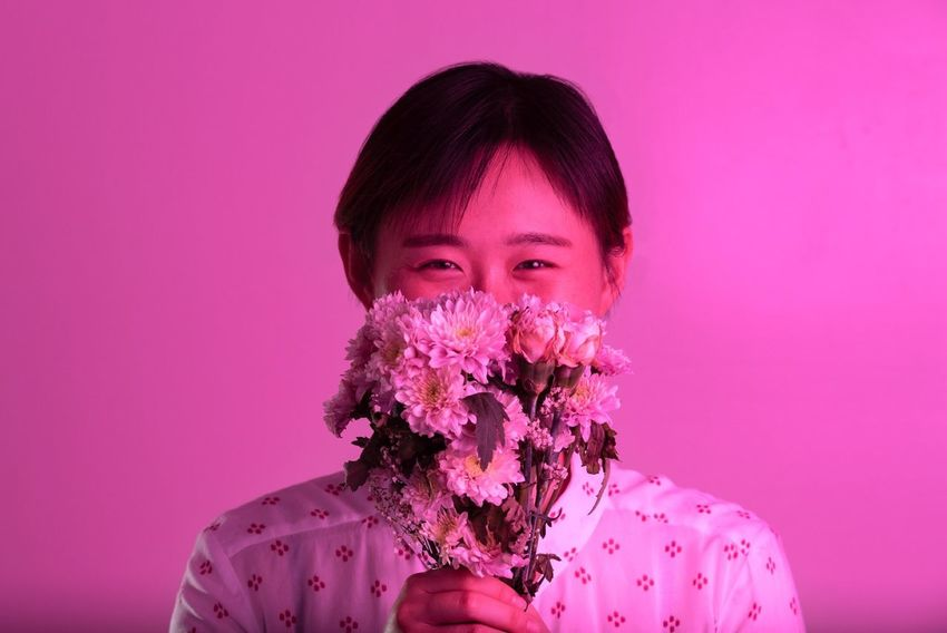 Portrait Of A Woman Portraiture Portrait Photography Portraits Mood People One Person Portrait Pink Color Headshot Studio Shot Looking At Camera Pink Background Colored Background Indoors  Young Adult Front View Flower Adult Freshness Flowering Plant Plant Lifestyles Human Face Purple