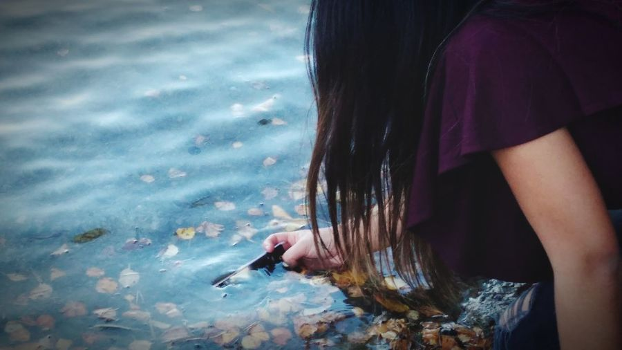 Midsection of woman touching water in lake