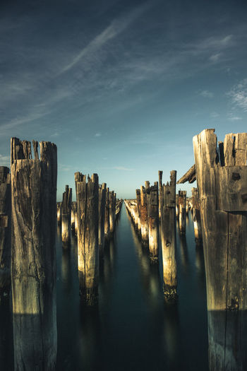 Panoramic view of wooden posts in lake against sky