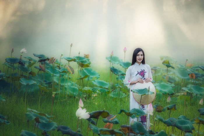 Woman dressed Vietnamese Vietnamese Beautiful Woman Beauty In Nature Day Dressed Flower Freshness Front View Growth Happiness Leaf Lifestyles Looking At Camera Nature One Person Outdoors People Plant Portrait Real People Sky Smiling Standing Young Adult Young Women
