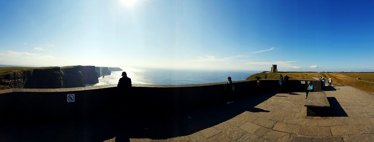 People at cliffs of moher against sea on sunny day