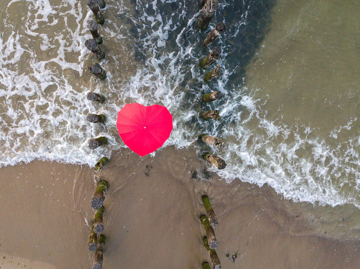 Directly Above Shot Of Heart Shape Umbrella Amidst Wooden Posts On Shore At Beach