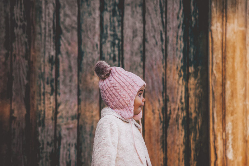 Close-up of toddler wearing knit hat standing by wooden wall