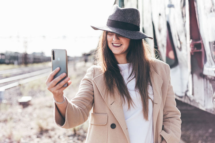 Young woman using mobile phone while standing on camera