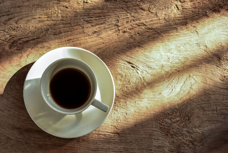 Cup of coffee on wood background highlighted by afternoon sunlight. The coffee cup last an hour. Afternoon Light Espresso Shade Shadows & Lights Textures And Surfaces Vintage Style Afternoon Coffee Close-up Coffee - Drink Coffee Cup Day Directly Above Drink Food Food And Drink Freshness Half Cup Of Coffee Hipster Indoors  No People Refreshment Relaxing Moments Saucer Table Window Light