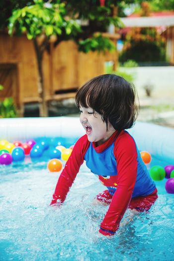 Boy playing with ball in swimming pool