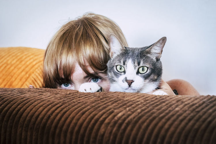 Portrait of boy with cat on sofa at home