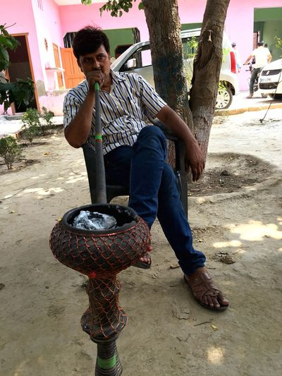 EyeEmSelect EyeEm Best Shots Eyee Premium Collection Full Length One Person Casual Clothing Young Adult Sitting Day Real People Outdoors Tree One Man Only Portrait One Young Man Only Smiling Only Men People Adults Only Adult Hookah Hookah Time  Tree Trunk Night Oil Lamp