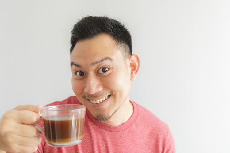 Portrait of smiling man holding drink against white background