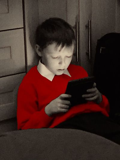 11 year old boy in school uniform on tablet. Faces In Places Tablet Child Boy Playing On His Tablet Red Jumper Relaxing Inside Portrait