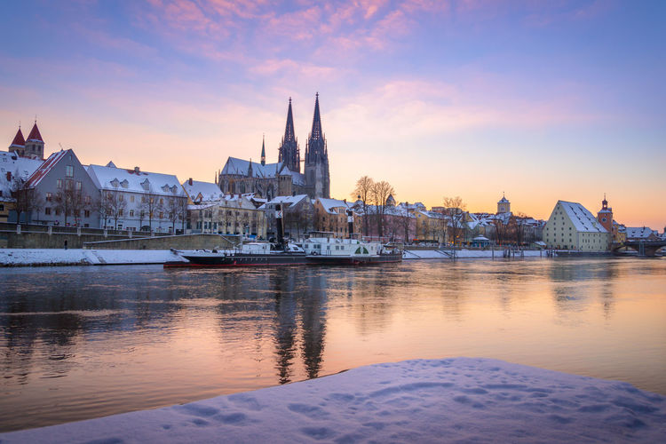 Regensburg cathedral and snow covered houses by danube river during sunset