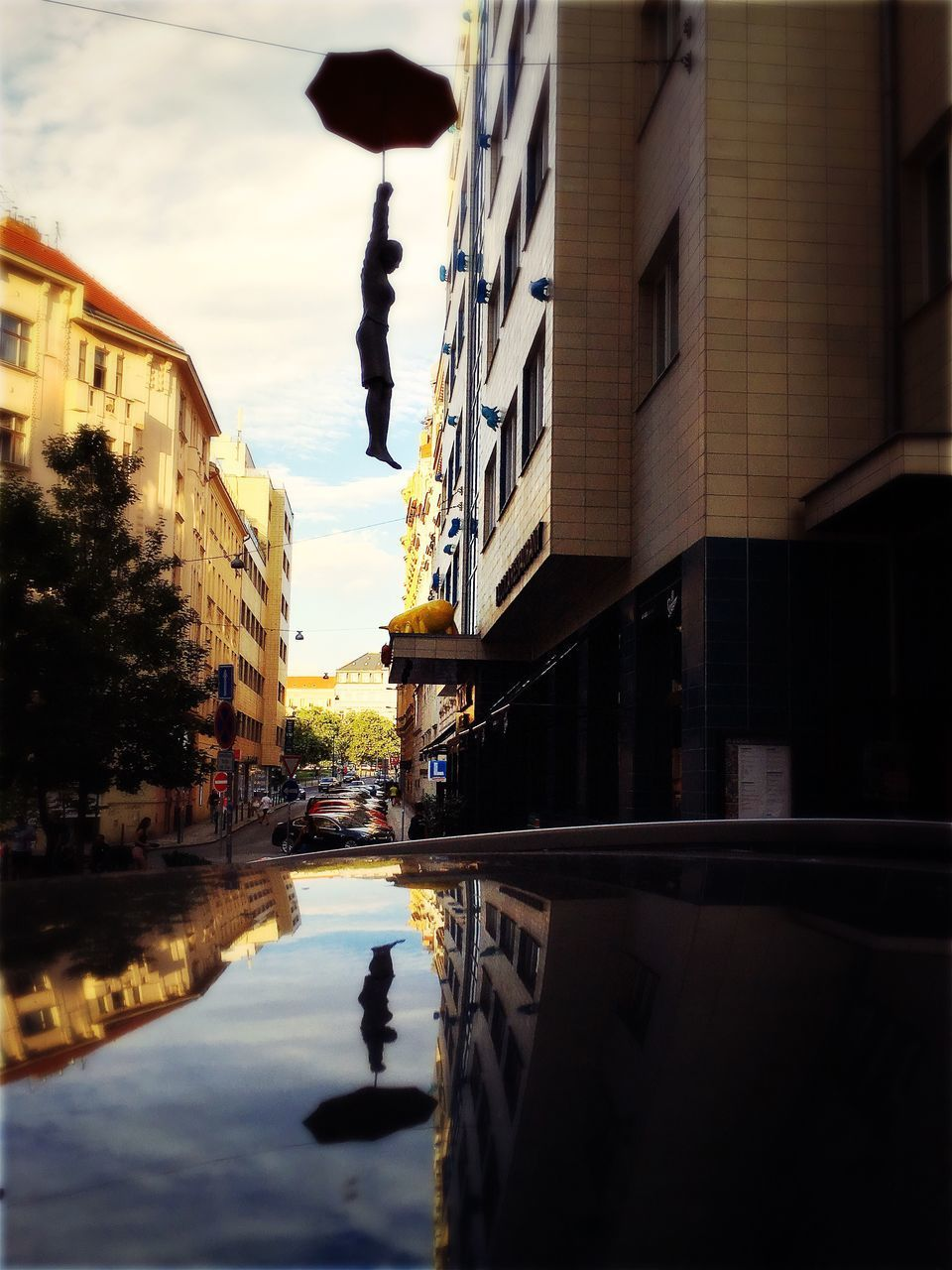 building exterior, architecture, built structure, city, reflection, water, building, puddle, transportation, sky, street, nature, mode of transportation, cloud - sky, real people, incidental people, residential district, outdoors, motor vehicle, canal, rain