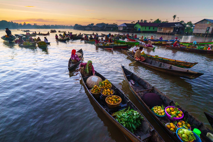 High angle view of people with food sitting in boats over river at sunset