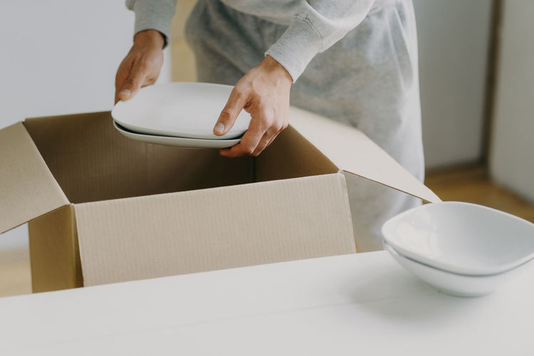Midsection of woman holding crockeries in new house