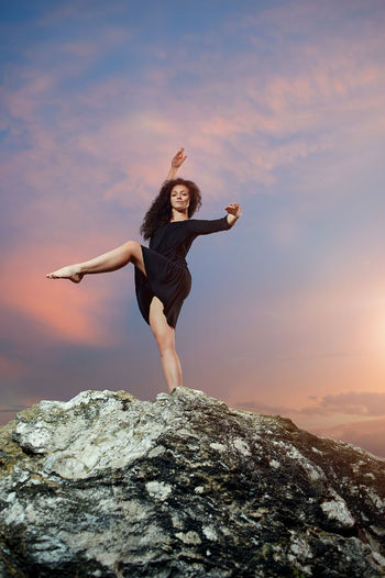 Full length of young woman standing on rock against sky during sunset