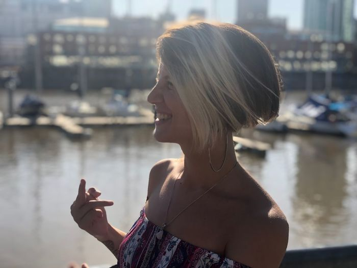 Smiling woman showing obscene gesture while standing in city