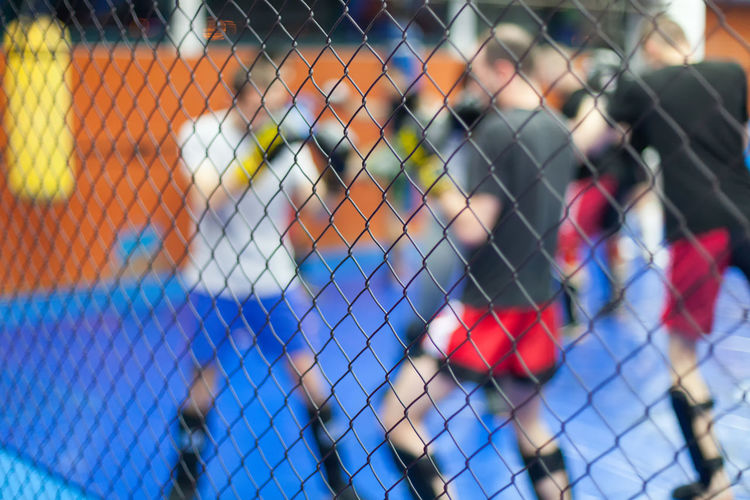 Men playing in court seen through chainlink fence