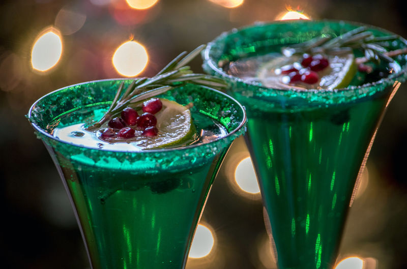 Close-up of champagne drink served with citrus fruit, rosemary and pomegranate seeds