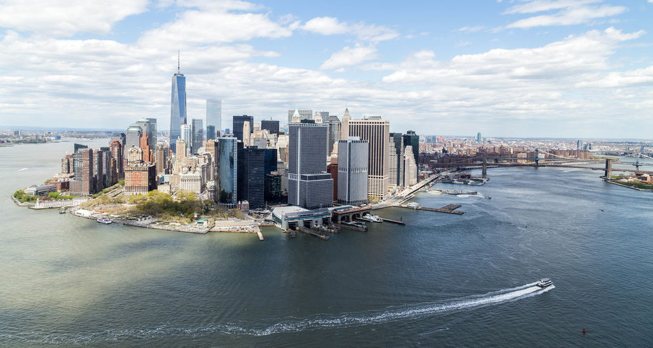 High angle view of east river by modern buildings against cloudy sky