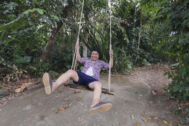 Portrait of man sitting on swing in forest