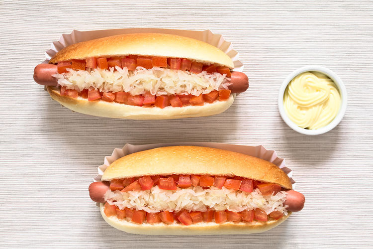 Chilean Completo Clasico (classical) or Completo Aleman (German) traditional hot dog sandwiches, made of bread, sausage, tomato cubes and sauerkraut, mayonnaise in small bowl on the side, photographed overhead with natural light completo Chilean  Completo Filled HotDog Roll Sandwich Bread Chilean Food Completo Aleman Completo Clasico Fast Food Food Food And Drink Fresh Freshness Hot Dog Meal Meat Processed Meat Ready-to-eat Relish Sauerkraut Sausage Snack Tomato