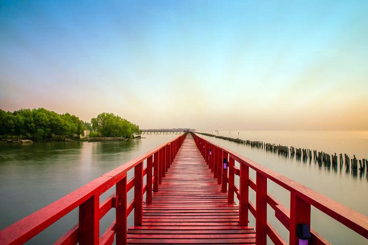 Wooden Bridge Over Calm Lake Against Sky