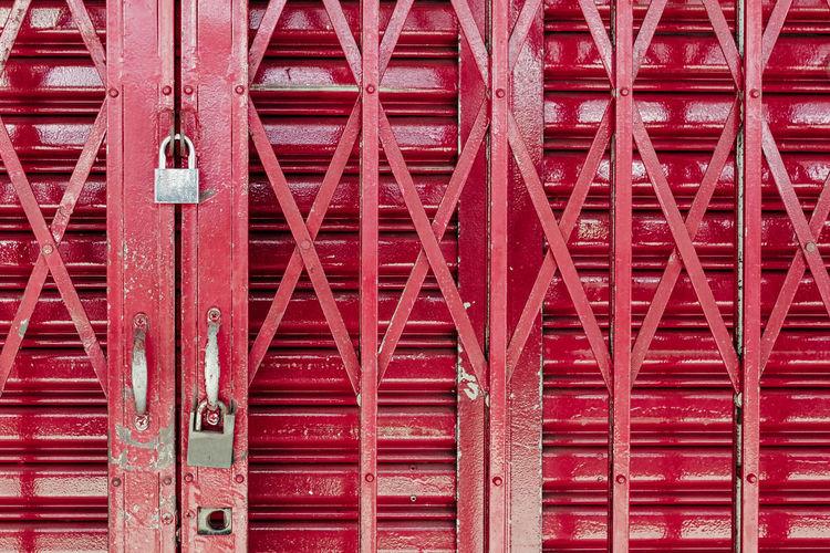 Close-up of padlocks hanging on metallic gate