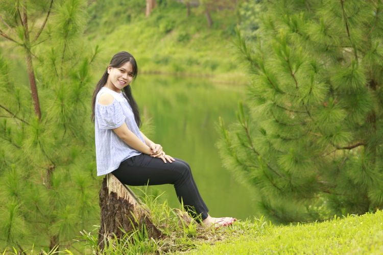 Full length of young woman sitting on land