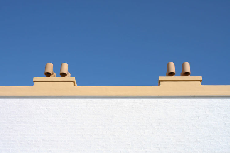 Whitewashed Wall Brick Wall Chimney Chimneys Architecture Blue Blue Sky Bricks Building Building Exterior Built Structure Clear Sky Copy Space Day House Low Angle View No Clouds No People Outdoors Roof Sky Sunlight Wall Wall - Building Feature White Color Whitewashed
