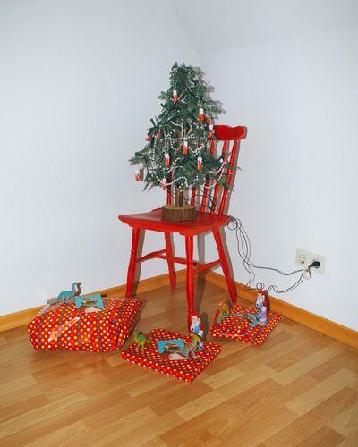 Christmas tree on hardwood floor against wall
