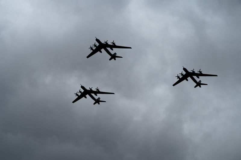 Low angle view of fighter planes flying against sky