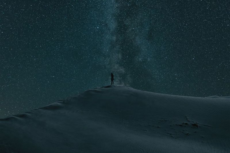 Person standing on snow covered landscape against star field