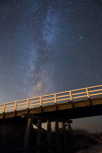 Low Angle View Of Illuminated Bridge Against Star Field