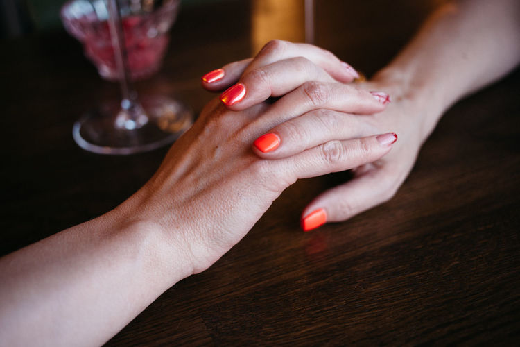 Cropped image of lesbians holding hands on table