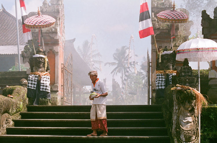 """not all that wander are lost"" 35mm Film Asian  Bali Balinese Architecture Palm Tree Sarong Smoke Traditional Clothing Agfa Vista200 Building Exterior Built Structure Day Elderly Man Film Photography Flag Full Length Holding Lifestyles Minimalism Mysterious One Person Outdoors Place Of Worship Real People Split Gate"