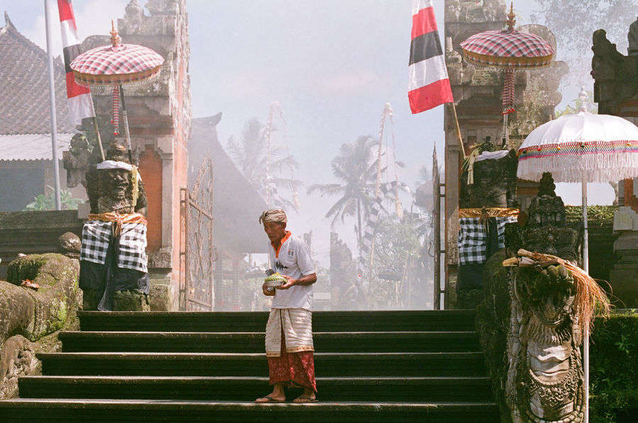 """""""not all that wander are lost"""" 35mm Film Asian  Bali Balinese Architecture Palm Tree Sarong Smoke Traditional Clothing Agfa Vista200 Building Exterior Built Structure Day Elderly Man Film Photography Flag Full Length Holding Lifestyles Minimalism Mysterious One Person Outdoors Place Of Worship Real People Split Gate"""