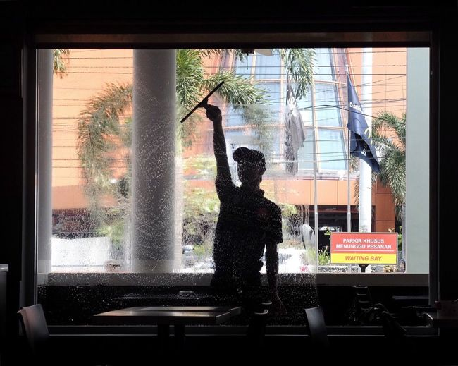 Silhouette of worker cleaning restaurant glass