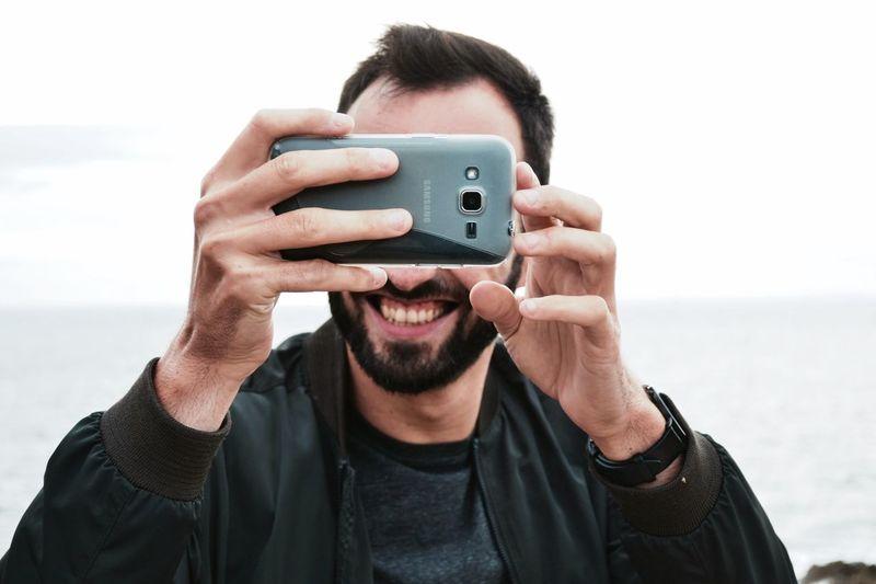 Portrait of man holding smart phone against sky