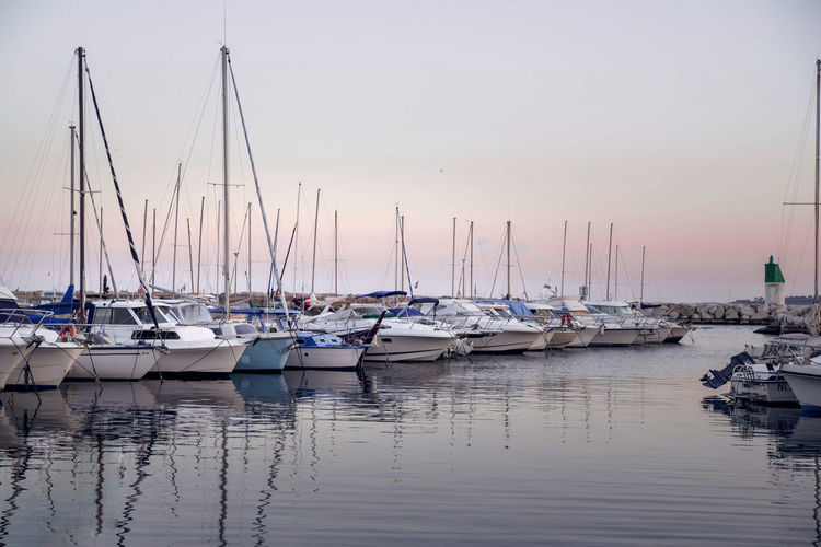 picturesque sunset with yachts at the pier on the coast, Cannes Riviera Nautical Vessel Water Mode Of Transportation Sailboat Transportation Moored Pole Sky Mast Reflection Harbor Waterfront No People Sunset Nature Sea Beauty In Nature Yacht Tranquility Marina Port Anchored Cannes