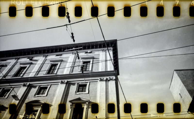 Urban power. Wrongly processed 35mm colour slide film (Rollei CR200), shot with a modified Holga. Analog Camera Analogue Analogue Photography Black & White Holga Holga Photography Power Lines Analog Analog Photography Architecture Building Exterior Built Structure Bw Cable City Looking Up Low Angle View No People Outdoors Power Line  Power Supply Rollei Sky Sprockets Urban
