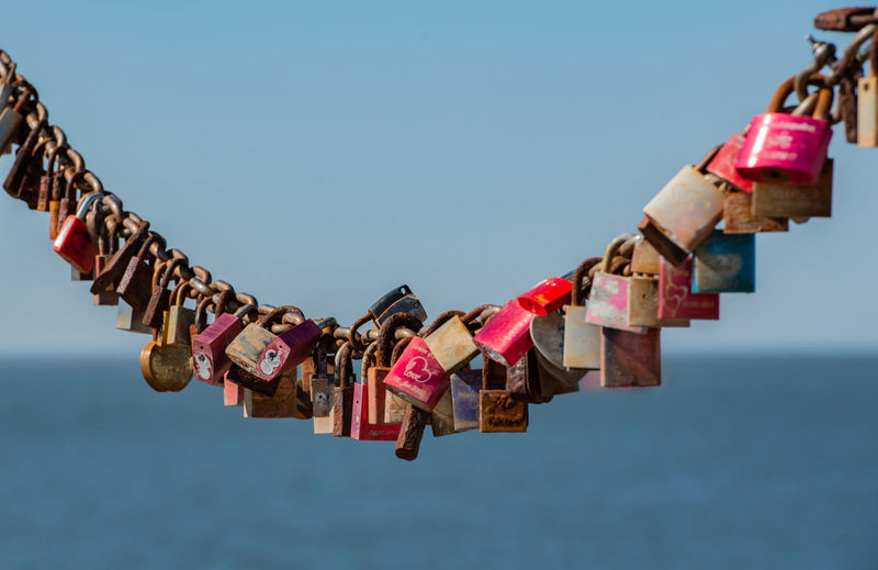 Close-up of love locks hanging on chain with sea in background