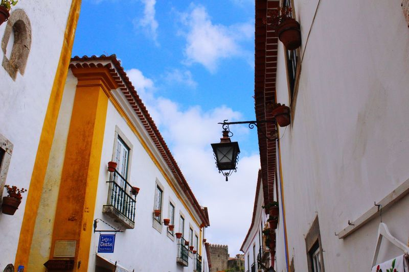 Building Exterior Architecture Built Structure Low Angle View Wall Lamp Day Window Residential Building Sky Outdoors No People Hanging Portugal Obidos Portugal Óbidos  Streetphotography Street Photography Hello World Live For The Story BYOPaper! The Street Photographer - 2017 EyeEm Awards The Architect - 2017 EyeEm Awards Paint The Town Yellow