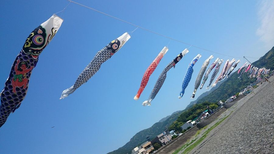 Low angle view of multi colored flags hanging against sky